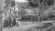 WS Shot of military camp as soldiers march on country road