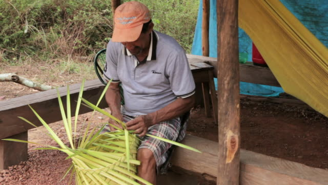 MS Shot of miners doing creative work with coconut leaves / Serra Pelada, Para, Brazil