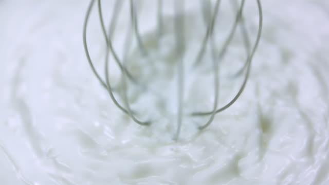 ECU SLO MO Shot of Mixer is rotating in milk / Toronto, Ontario, Canada
