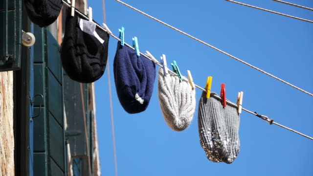 MS LA Shot of monkey cap hanging on wire outside houses, Arsenale / Venice, Veneto, Italy