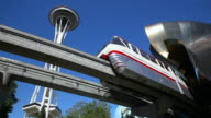 MS Shot of LA Monorail with Space Needle and Experience Music Project / Seattle, Washington, United States