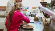 MS Shot of mother and daughter baking together in kitchen / Lamy, New Mexico, United States