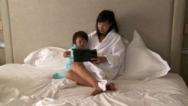 MS Shot of mother and his little girl playing on digital tablet / Marbella, Andalusia, Spain