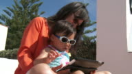MS Shot of mother and his little girl using digital tablet / Marbella, Andalusia, Spain