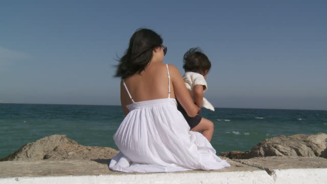 MS Shot of mother and his little girl watching waves / Marbella, Andalusia, Spain