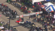 MS AERIAL TS ZO Shot of motorcycles parked in downtown street with Welcome Bikers sign and pull out of festival / Sturgis, South Dakota, United States