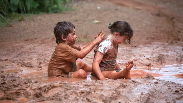 MS PAN Shot of muddy little girl and boy rolling around in mud puddle then little boy putting mud cakes on little girls back / Montezuma, Punteranes, Costa Rica