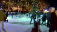'MS T/L Shot of Natural History Museum Ice Skating Rink Londo at Night, skaters passing and trees with Xmas lights in back side / London, Greater London, United Kingdom'