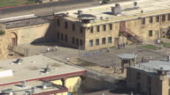 MS AERIAL Shot of Nevada State Prison campus and prisoners playing basketball on outside court on sunny day / Carson City, Nevada, United States