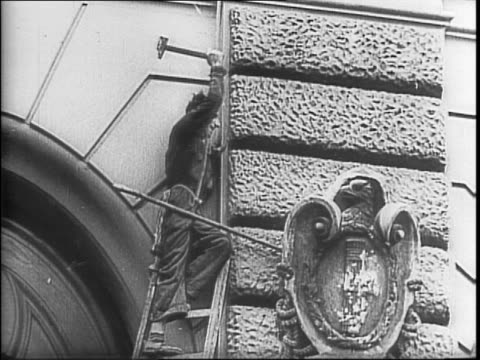 Shot of newspaper article with photo of Benito Mussolini / montage of men removing Fascist emblems from a building with hammers / crowds of Italian...