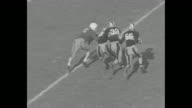 Shot of newspaper headline 'Army And Notre Dame Win 148 140' / Yale and Army teams run on field one player tackles another / new play and scrimmage...