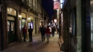 MS PAN Shot of Night in small alleys and windows of typical restaurant of center of town / Santiago de Compostela, Spain