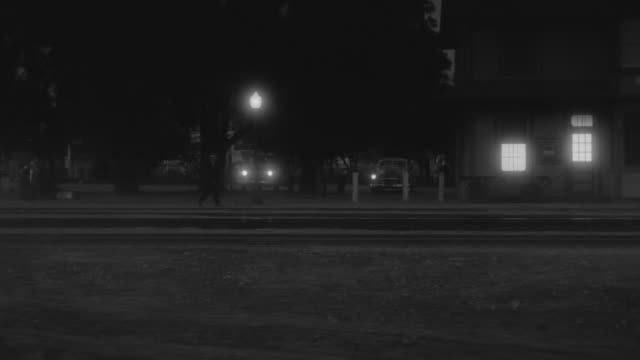 MS TS PAN Shot of nondescript street in small town at intersection of railroad crossing, Car drive on street at night