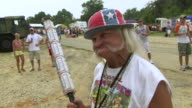 CU ZI Shot of old man making funny face with holding torch made of Budweiser cans during Summer Redneck Games / Dublin, Georgia, United States