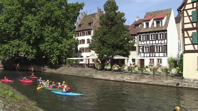 MS Shot of Old town Petite France, people enjoying kayak at ILL River at Quai de la Bruch / Strasbourg, Alsace, France