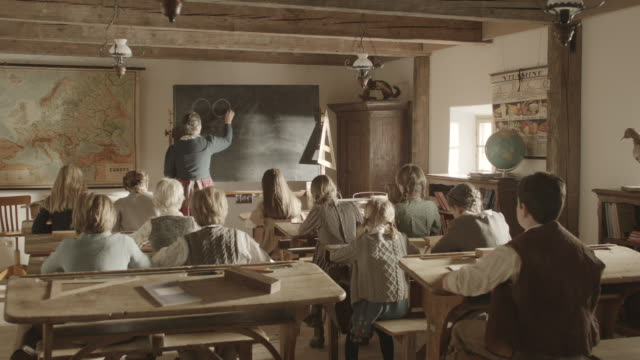 MS PAN Shot of old woman writing something on blackboard in classroom with children sitting on desk / Grossweil, Bavaria, Germany