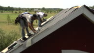 MS Shot of one worker moving shingles while another is hammering on roof of red building / Chelsea, Michigan, United States
