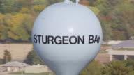 CU AERIAL ZO Shot of orbit around water tower with Sturgeon Bay sign / Sturgeon Bay, Wisconsin, United States