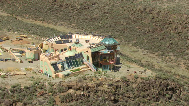 MS AERIAL DS ZI Shot of orbit Earthships house that looks like castle made of natural and recycled materials in Taos County / New Mexico, United States