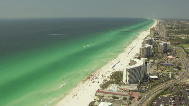 WS AERIAL Shot of orbit hotel and people on beach / Panama City, Florida, United States