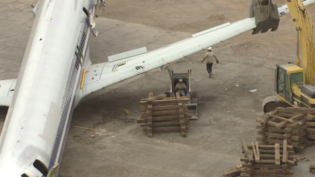MS AERIAL Shot of orbit MD80 commercial jet airliner claw grabs wing and workers remove supports
