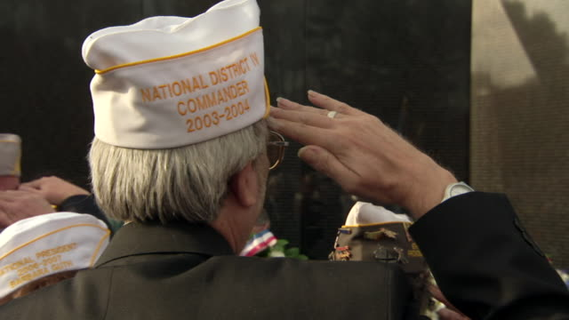 MS Shot of OTS Veteran wearing white cap salutes in front of Vietnam Veterans Memorial Wall / Washington, District of Columbia, United States