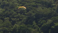 MS AERIAL TS  R/F Shot of paraglider by mountain range / Rio de Janeiro, Brazil