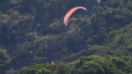 MS AERIAL TS  Shot of paraglider by mountain range / Rio de Janeiro, Brazil