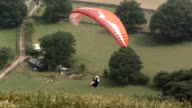 MS PAN SLO MO Shot of paraglider flying above hill tops