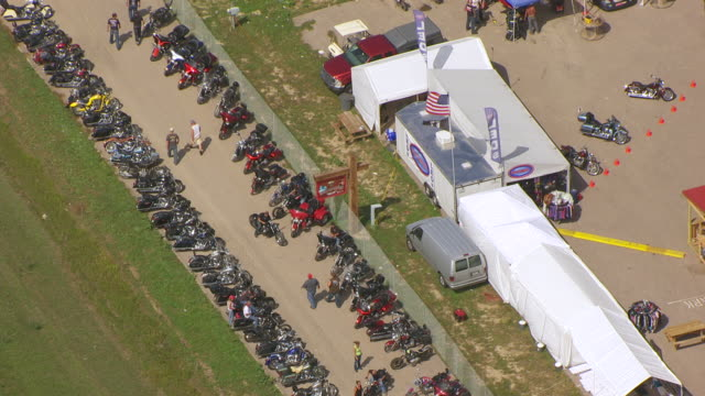 MS AERIAL TS ZO PAN Shot of parking lot with rows of motorcycles and pull out to Broken Spoke Saloon in Meade County / Sturgis, South Dakota, United States