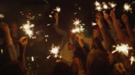 'MS PAN Shot of Party with group of young people and band on rooftop, lighting and holding sparklers, dancing, playing music / Berlin, Germany'