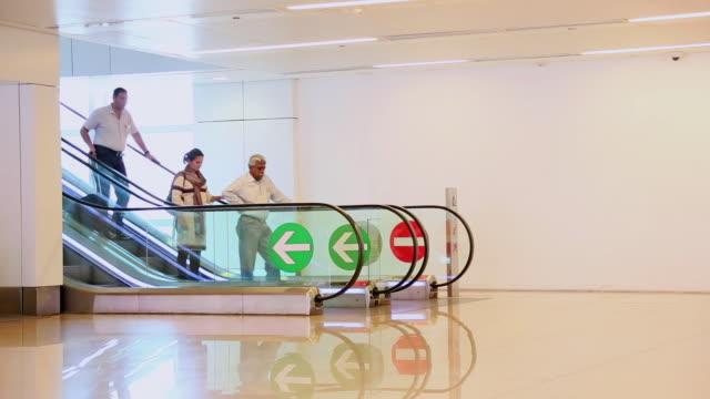 MS Shot of Passenger getting come down at escalator in Indira Gandhi International Airport / Delhi, India