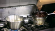 MS TD Shot of pastry chef mixing chocolate glaze on cooker with reflection in mirror / Rome, Lazio, Italy