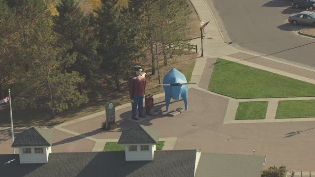 MS AERIAL ZO Shot of Paul Bunyan and Babe statues and pull out to reveal Lake / Bemidji, Minnesota, United States