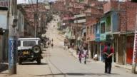 WS Shot of pedestrians walking on hilly street in Ciudad Bolivar slum / Bogota, Colombia