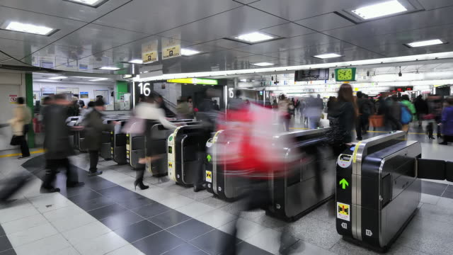MS T/L Shot of people crowd passing through JR train station ticket system / Tokyo, Japan