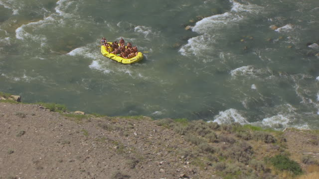 MS AERIAL Shot of people enjoying at river rafters going down rapids of the Shoshone River / Wyoming, United States