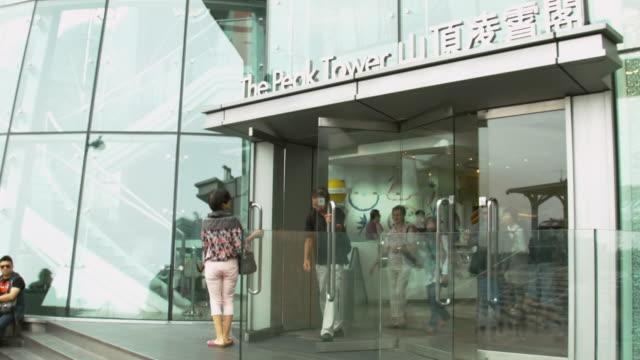 MS Shot of People exiting Peak Tram Tower / Hong Kong, China