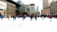 Shot of people on the ice rink at city hall plaza in front of town hall built structure