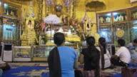 MS Shot of People praying to golden Buddha statue / Yangon, Yangon Division, Myanmar