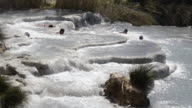 WS Shot of People relaxing in hot spring, thermal pools of sulphurous water / Saturnia, Tuscany, Italy