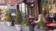 MS T/L Shot of People sit at and passing by coffee shop in Bowery neighborhood during day / New York ,United States