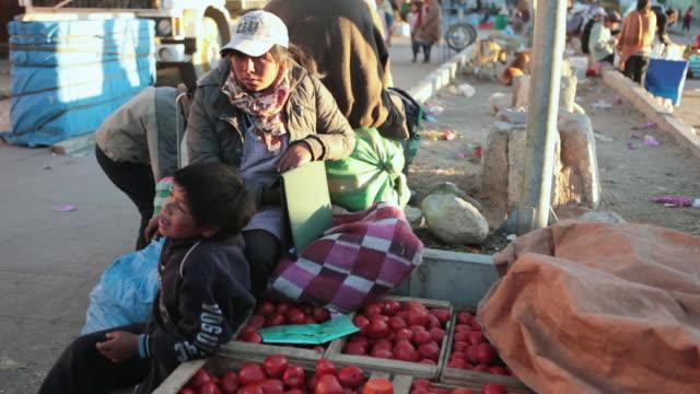 MS Shot of people sitting near fruit stall at Potosi food fair / Potosi Bolivia