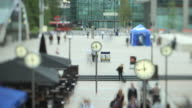 MS T/L Shot of people walking and clocks in Canary Wharf / London, Greater London, United Kingdom