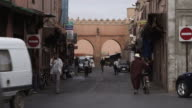 MS Shot of people walking and vehicles moving on street / Marrakesh, Morocco