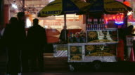 MS Shot of People walking by hot dog stand on street at night / New York, United States