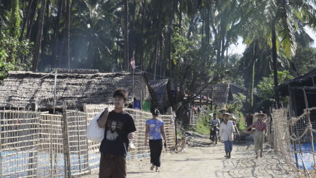 MS Shot of People walking in fishing village / Ngapali, Rakhine State, Myanmar