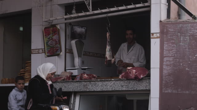 MS Shot of people walking on street and souk meat vendor selling meat / Marrakesh, Morocco