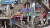 WS Shot of people walking up and down overpass stairs in busy street / Dhaka, Bangladesh