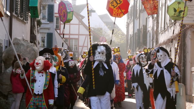 WS Shot of people with mask and dressing celebrating Basler Fasnacht (Basel Carnival) on street / Basel, Switzerland